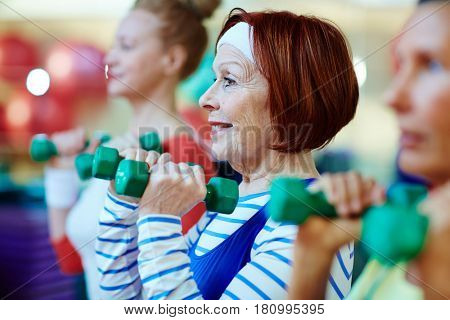 Energetic females exercising with dumbbells