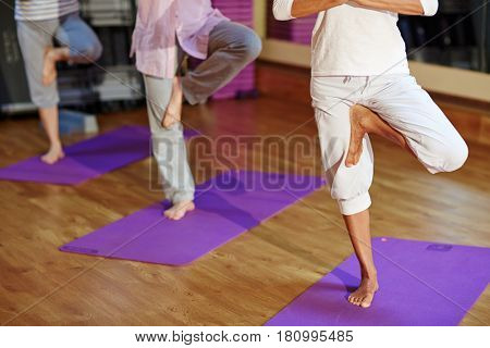 Three humans standing on one leg during yoga exercise