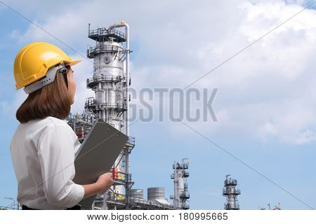 Female Engineer Wearing Safety Helmet Inspects Pipeline Industry Site