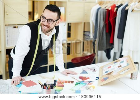 Happy clothier standing by his workplace in studio of fashion
