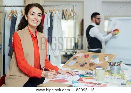 Elegant designer making sketches in notepad