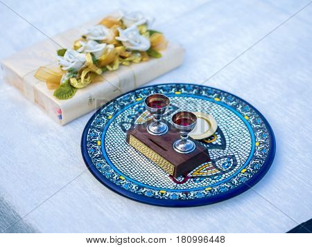 Wine and Host on Ceramic Plate beside Bible