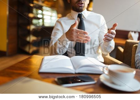 Businessman gesticulating during talk with co-workers