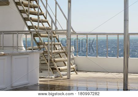 Boat ladder, Deck on the stern of the yacht on a bright sunny day and beautiful blue sea water.