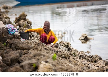 Cebu, Philippines - September 29, 2014. People gather plankton, crabs on the sea