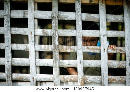 Cebu, Philippines - September 29, 2014. Sad child play in a cage. Everyday life of filipinos