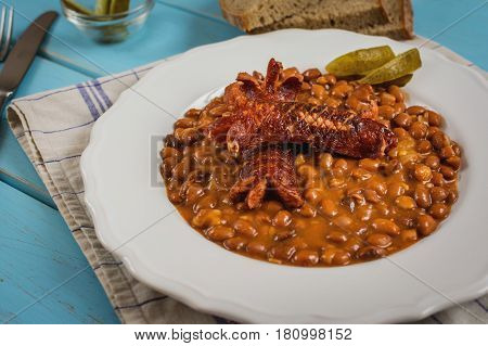 Red beans with sauce and grilled sausage on blue table