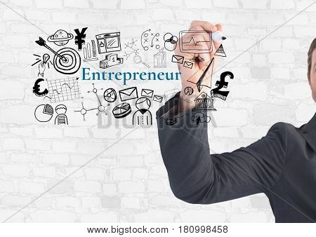 Digital composite of Businessman writing Entrepeneur text with drawings graphics