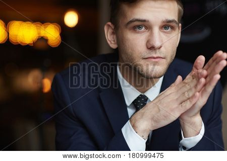Portrait of young pensive businessman looking away with serious neutral expression and rubbing hands restlessly