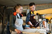 Waist-up portrait of attractive apprentice standing at drill press and listening to her male mentor with attention, he explaining her operating principle of machine poster