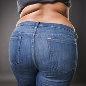 Woman with fat buttocks in blue jeans overweight female body closeup gray studio background poster
