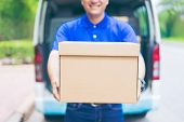 Delivery concept - Smiling happy young asian handsome male postal delivery courier man in front of cargo van delivering package holding box with service mind and blue uniform poster