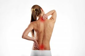 Tired woman massaging back and neck muscles. Health care and medicine.