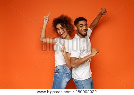 Young Lovely African-american Couple Standing Together And Laughing, Posing On Orange Background, Co