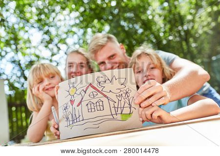 Happy family shows a colorful home drawing as a motive