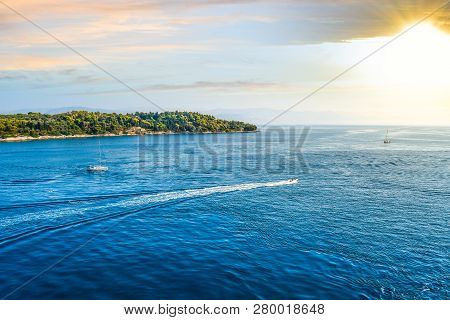 Two Small Sailboats Head Towards The Setting Sun Beaten Greek Islands Off The Coast Of Corfu, Greece