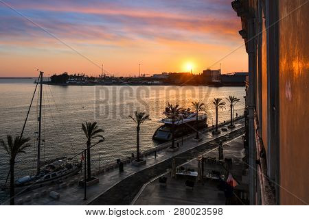 Brindisi, Italy - September 22 2018: The Sun Sets Over The Harbor Port As Boats Dock Along The Water