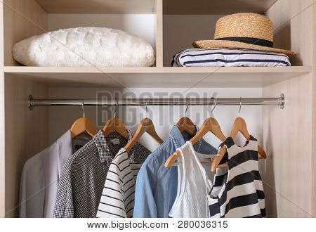 Collection Of Stylish Clothes And Pillow In Wardrobe Closet