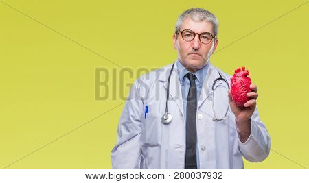 Handsome senior cardiologist doctor man holding heart over isolated background with a confident expression on smart face thinking serious