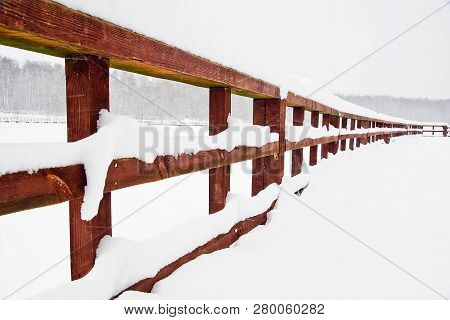 Wooden Fence In A City Park In Winter
