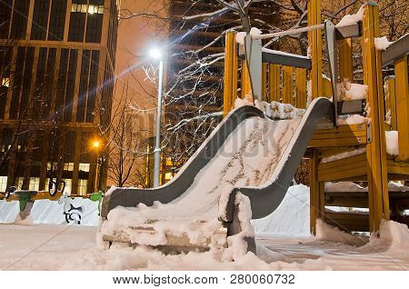 Children's Slide In The Snow In The Evening