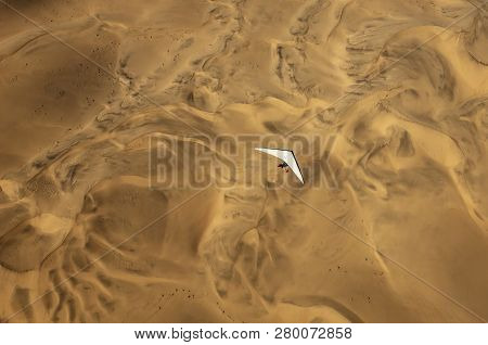 An Ultralight Aircraft Can Be Seen Flying Over The Sands Of Namibia