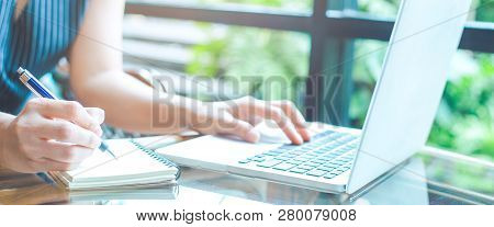 Business Woman Hand Is Writing On A Notepad With A Pen And Using A Laptop Computer.
