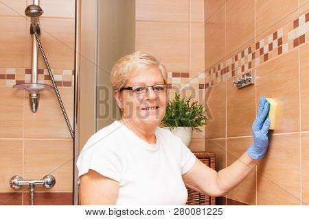 Elderly Senior Woman In Protective Rubber Gloves Washing Tiles In Bathroom Using Sponge, Concept Of