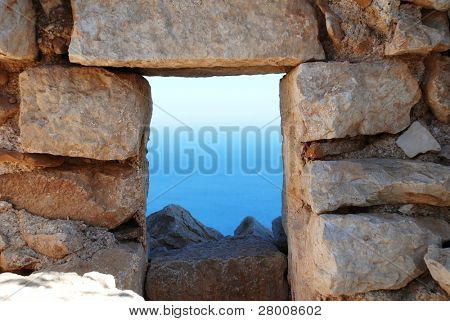 Looking through the window of the medieval Knights of Saint John crusader castle near Horio on the Greek island of Halki.