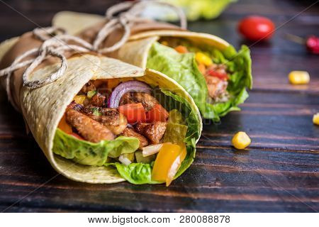 Traditional Mexican Tortilla Wrap With Vegetables And Grilled Chicken Meat On Dark Wood Table