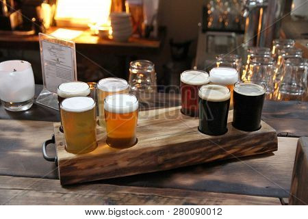 Eight Beer Samples In A Burned Wood Holder On A Burned Wood Table In A Warm Room.