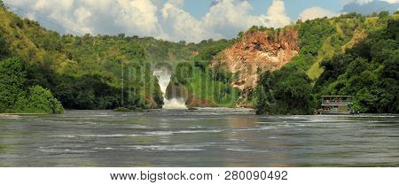 A Panoramic Shot Of Murchison Falls With A River Cruise Boat And The Surrounding River And Jungle.