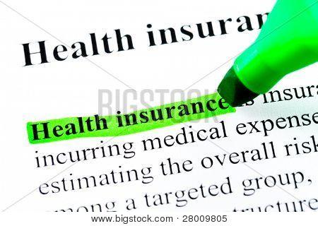 Definição de seguro de saúde destacada pelo marcador verde sobre fundo branco papel
