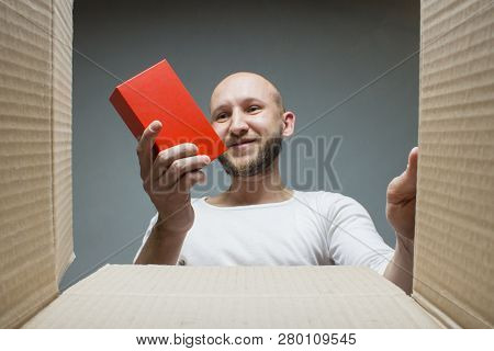 A Man With A Happy Face Holds The Goods Received. Inside View. The Concept Received A Parcel, An Ord