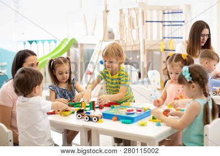 Kindergarten Children Playing Toys With Teacher In Playroom At Preschool. Education Concept.