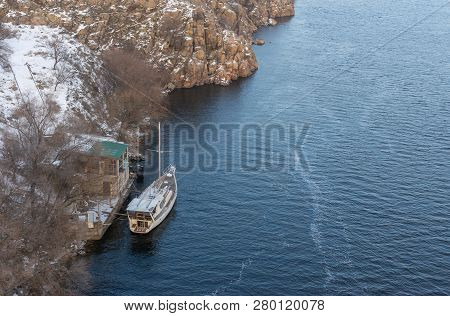 Lonely Yacht An A Winter Anchorage To Rocky Dnipro Riverside In Zaporizhia City, Ukraine