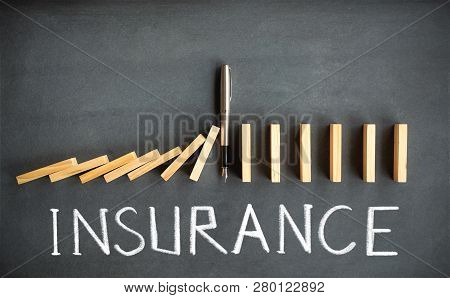 Chain Reaction And Insurance Concept With Dominoes Toppling On Blackboard