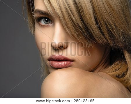 Blone woman with a short hair, fringe.  Sexy blonde woman.  Attractive blond model with blue eyes. Fashion model with a smokey makeup. Closeup portrait of a pretty woman. Creative short hairstyle.