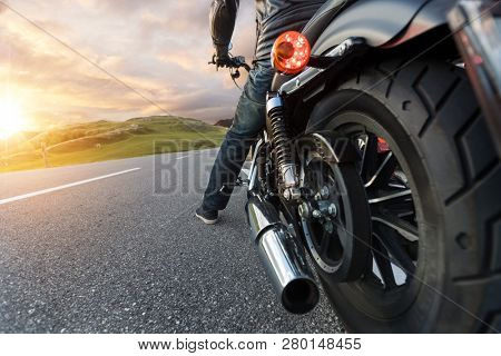 Detail of motorcycle rider driving in Alpine road.