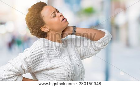 Beautiful young african american woman wearing sweater over isolated background Suffering of neck ache injury, touching neck with hand, muscular pain