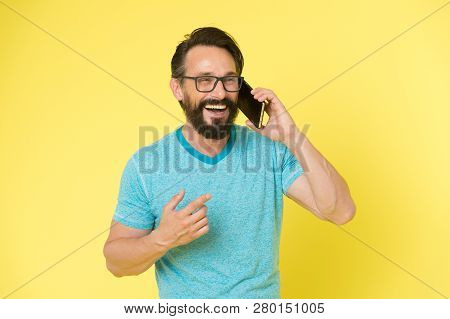 Stay In Touch. Man Bearded Cheerful Mature Guy Hold Mobile Phone Yellow Background. Hipster Smartpho
