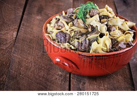 Venison Or Beef Mushroom Stroganoff With In A Red Ceramic Serving Bowl Garnished With Fresh Dill Ove