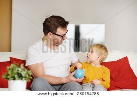 Father And Son Putting Coin Into Piggy Bank. Education Of Children In Financial Literacy.