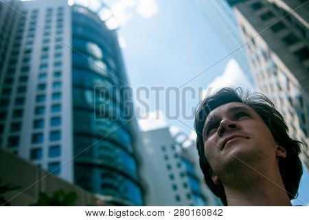 Young Man On The Background Of Skyscrapers, Looking Up. Ambitious People In The Corporate World, Con