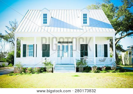 Small White Beach Cottage With A Metal Roof, Dormer Windows, And Black Shutters.