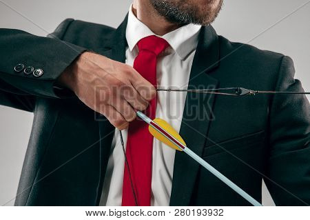 Businessman Aiming At Target With Bow And Arrow Isolated On Gray Studio Background. The Business, Go