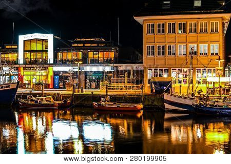 Warnemunde Rostock, Germany - September 5 2018: Illuminated Shops And Cafes In The Evening As Boats