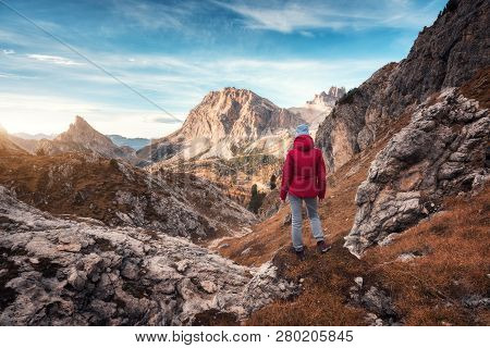 Young Woman On The Trail Looking On High Mountain Peak At Sunset In Dolomites, Italy. Autumn Landsca