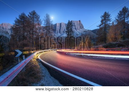 Blurred Car Headlights On Winding Road At Night In Autumn. Landscape With Asphalt Road, Light Trails