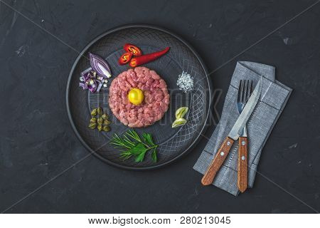 Steak Tartare With Yolk And Ingredients On Black Ceramic Plate, Set Of Cutlery Knife And Fork On Bla